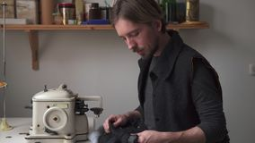 Νέος όμορφος ράφτης ατόμων που χαμογελά στο ράψιμο του εργαστηρίου φιλμ μικρού μήκους