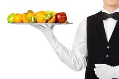 Νέος όμορφος σερβιτόρος που κρατά το μεγάλο σύνολο δίσκων των νωπών καρπών Στοκ Εικόνες