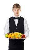 Νέος όμορφος σερβιτόρος που κρατά το μεγάλο σύνολο δίσκων των νωπών καρπών Στοκ Εικόνα
