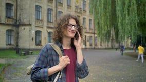 Νέος όμορφος σπουδαστής με τη μακριά σγουρή τρίχα που μιλά στο τηλέφωνο και που στέκεται στην οδό κοντά στο κολλέγιο, ημέρα, υπαί απόθεμα βίντεο