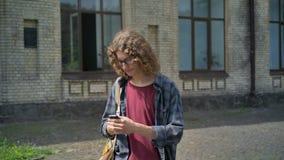 Νέος όμορφος σπουδαστής με το σακίδιο πλάτης που πηγαίνει μακρυά από το κολλέγιο και που στο τηλέφωνο, που περπατά στην οδό κοντά απόθεμα βίντεο