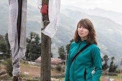 Νέος όμορφος τουρίστας γυναικών που στέκεται τις βουδιστικές σημαίες προσευχής Στοκ φωτογραφία με δικαίωμα ελεύθερης χρήσης