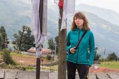 Νέος όμορφος τουρίστας γυναικών που στέκεται τις βουδιστικές σημαίες προσευχής Στοκ Φωτογραφίες