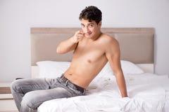 Νέος όμορφος τύπος γυμνοστήθων που παρουσιάζει nude κορμό προκλητικό στο κρεβάτι στο χ Στοκ Φωτογραφίες