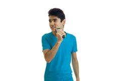 Νέος όμορφος τύπος σε μια μπλούζα που κοιτάζουν λοξά και το πρόσωπο μηχανών ξυρίσματος ξυρισμάτων Στοκ Εικόνες