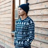 Νέος όμορφος τύπος στο πουλόβερ χειμερινών Χριστουγέννων στο υπόβαθρο Στοκ Εικόνες