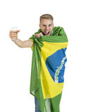 Νέος όμορφος υποστηρικτής της Βραζιλίας που κρατά ψηλά την μπύρα ενθαρρυντική με τη σημαία της Βραζιλίας Στοκ Φωτογραφία