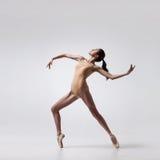 Νέος όμορφος χορευτής μπαλέτου στο μπεζ μαγιό στοκ εικόνες