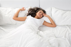 Νέος ύπνος γυναικών στο άσπρο λινό στο κρεβάτι στοκ φωτογραφία
