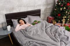 Νέος ύπνος γυναικών στο κρεβάτι και χριστουγεννιάτικο δώρο που βρίσκεται πλησίον στοκ φωτογραφία με δικαίωμα ελεύθερης χρήσης