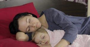 Νέος ύπνος μητέρων με την λίγη κόρη μωρών Οικογενειακός ύπνος στο κρεβάτι φιλμ μικρού μήκους