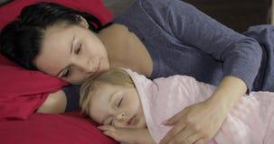 Νέος ύπνος μητέρων με την λίγη κόρη μωρών Οικογενειακός ύπνος στο κρεβάτι απόθεμα βίντεο