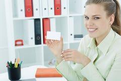 Νέος smilling γραμματέας που παρουσιάζει κενό κενό σημάδι καρτών εγγράφου με το διάστημα αντιγράφων για το κείμενο Στοκ Φωτογραφία