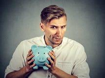 Νέο άπληστο φιλάργυρο επιχειρησιακό άτομο που κρατά τη piggy τράπεζα Στοκ Φωτογραφίες