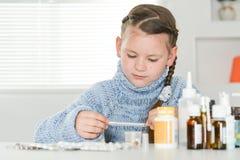 Νέο άρρωστο κορίτσι με τη συνεδρίαση θερμομέτρων Στοκ Εικόνα
