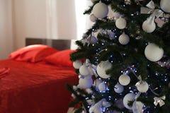 Νέο άσπρο δωμάτιο Χριστουγέννων έτους με το κόκκινο χριστουγεννιάτικο δέντρο διακοσμήσεων Στοκ Εικόνα