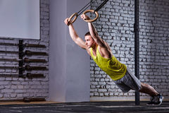 Νέο άτομο αθλητών που επιλύει στο τράβηγμα UPS γυμναστικής με τα γυμναστικά δαχτυλίδια ενάντια στο τουβλότοιχο στη διαγώνια κατάλ Στοκ εικόνα με δικαίωμα ελεύθερης χρήσης
