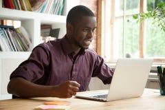 Νέο άτομο αφροαμερικάνων που εξετάζει το lap-top που ματαιώνεται από το κακό ν Στοκ Φωτογραφίες