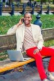 Νέο άτομο αφροαμερικάνων που μιλά στο τηλέφωνο κυττάρων, που λειτουργεί στην περιτύλιξη στοκ φωτογραφίες