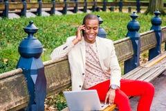 Νέο άτομο αφροαμερικάνων που μιλά στο τηλέφωνο κυττάρων, που λειτουργεί στην περιτύλιξη στοκ φωτογραφία