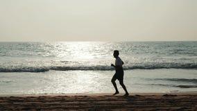 Νέο άτομο δρομέων αθλητών τουριστών σπουδαστών σκιαγραφιών με την κατάλληλη ισχυρή κατάρτιση σωμάτων στην όμορφη άμμο παραλιών θε απόθεμα βίντεο