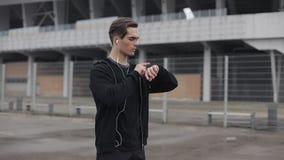Νέο άτομο δρομέων που χρησιμοποιεί το έξυπνο ρολόι ιχνηλατών ικανότητας πριν από το workout κοντά στο στάδιο Νεφελώδης καιρός, απόθεμα βίντεο