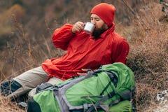 Νέο άτομο εξερευνητών που πίνει το καυτό ποτό στα βουνά, τη συνεδρίαση και τη χαλάρωση μετά από την οδοιπορία στοκ φωτογραφία
