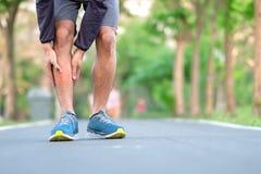 Νέο άτομο ικανότητας που κρατά τον τραυματισμό αθλητικών ποδιών του μυς επίπονος κατά τη διάρκεια της κατάρτισης Ασιατικός δρομέα στοκ εικόνα με δικαίωμα ελεύθερης χρήσης