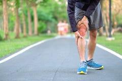 Νέο άτομο ικανότητας που κρατά τον τραυματισμό αθλητικών ποδιών του μυς επίπονος κατά τη διάρκεια της κατάρτισης Ασιατικός δρομέα στοκ φωτογραφία