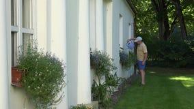 Νέο άτομο κηπουρών στα σορτς που ποτίζει τα δοχεία λουλουδιών στις στρωματοειδείς φλέβες παραθύρων σπιτιών κήπων 4K απόθεμα βίντεο