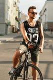 Νέο άτομο hipster με τη συνεδρίαση ποδηλάτων σε ένα ποδήλατο στην πόλη Στοκ εικόνες με δικαίωμα ελεύθερης χρήσης