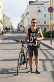 Νέο άτομο hipster με το ποδήλατο που περπατά στην πόλη Μαύρο τ -τ-shir Στοκ Φωτογραφία