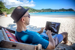 Νέο άτομο hipster με το lap-top στην τροπική παραλία Ταξίδι, vacatio Στοκ εικόνες με δικαίωμα ελεύθερης χρήσης