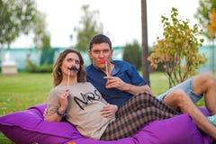 Νέο έγκυο ζεύγος - αγκαλιάσματα υπαίθρια με τις μάσκες Στοκ Φωτογραφία