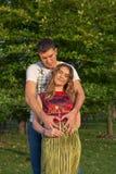 Νέο έγκυο ζεύγος - αγκαλιάσματα υπαίθρια Στοκ Εικόνες