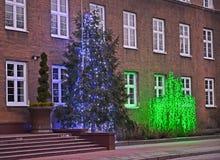 Νέο δέντρο έτους και το λάμποντας δέντρο στα πλαίσια του κτηρίου Στοκ φωτογραφία με δικαίωμα ελεύθερης χρήσης