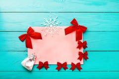 νέο έτος έννοιας Χριστου&gamm Πλαίσιο των κόκκινων τόξων με τα χειμερινά εξαρτήματα στο μπλε ξύλινο υπόβαθρο Τοπ όψη στοκ εικόνες με δικαίωμα ελεύθερης χρήσης