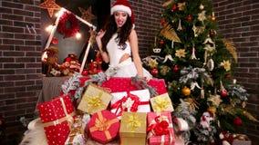 Νέο έτος με το εύθυμο και όμορφο κορίτσι, δώρα Χριστουγέννων για τα παιδιά, ένα φιλί αέρα από το βοηθό Santa ` s φιλμ μικρού μήκους