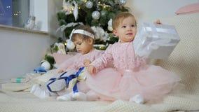 Νέο έτος, οι μικρές αδελφές στα ρόδινα φορέματα κάθονται στο καρό με τα κιβώτια δώρων στα πλαίσια του χριστουγεννιάτικου δέντρου  απόθεμα βίντεο