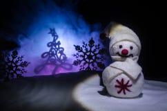 νέο έτος Ο χιονάνθρωπος ξεφορτώνει τα δώρα για το νέο έτος Χιονάνθρωπος που περιβάλλεται λευκός από τα χριστουγεννιάτικα δέντρα σ Στοκ εικόνα με δικαίωμα ελεύθερης χρήσης