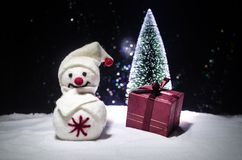 νέο έτος Ο χιονάνθρωπος ξεφορτώνει τα δώρα για το νέο έτος Χιονάνθρωπος που περιβάλλεται λευκός από τα χριστουγεννιάτικα δέντρα σ Στοκ φωτογραφία με δικαίωμα ελεύθερης χρήσης