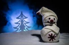 νέο έτος Ο χιονάνθρωπος ξεφορτώνει τα δώρα για το νέο έτος Χιονάνθρωπος που περιβάλλεται λευκός από τα χριστουγεννιάτικα δέντρα σ Στοκ Εικόνες
