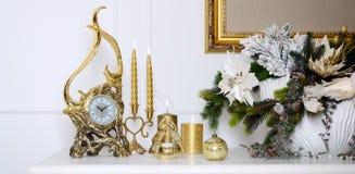 νέο έτος σύνθεσης Χριστο&upsi Διακοσμητικό χρυσό ρολόι, παχιά κεριά, κηροπήγιο, δοχείο των λουλουδιών και πλαισιωμένος καμβάς που Στοκ Εικόνα