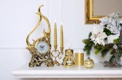 νέο έτος σύνθεσης Χριστο&upsi Διακοσμητικό χρυσό ρολόι, παχιά κεριά, κηροπήγιο, δοχείο των λουλουδιών και πλαισιωμένος καμβάς που Στοκ φωτογραφία με δικαίωμα ελεύθερης χρήσης