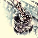νέο έτος Χριστουγέννων χύνοντας κόκκινο κρασί κρασί γυαλιού εκλεκτική εστίαση, θαμπάδα κινήσεων, κόκκινο κρασί σε ένα γυαλί Κρασί Στοκ Εικόνες