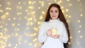 νέο έτος Χριστούγεννα Η όμορφη γυναίκα σε ένα θερμό άσπρο πουλόβερ κρατά στα χέρια που ένας λαμπτήρας, κλείνει τα μάτια του και ν απόθεμα βίντεο