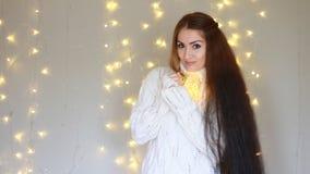 νέο έτος Χριστούγεννα Η όμορφη γυναίκα σε ένα θερμό άσπρο πουλόβερ κρατά στα χέρια που ένας λαμπτήρας, κλείνει τα μάτια και να ον απόθεμα βίντεο