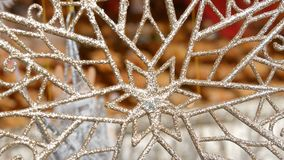 Νέο έτος ` s και ντεκόρ Χριστουγέννων Τεράστιο όμορφο ασημένιο snowflake ταλαντεύεται στον αέρα στην αγορά Χριστουγέννων φιλμ μικρού μήκους