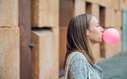 Νέο έφηβη που φυσά τη ρόδινη γόμμα φυσαλίδων στοκ φωτογραφία