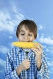Νέο αγροτικό αγόρι που τρώει το βρασμένο καλαμπόκι Στοκ Φωτογραφία